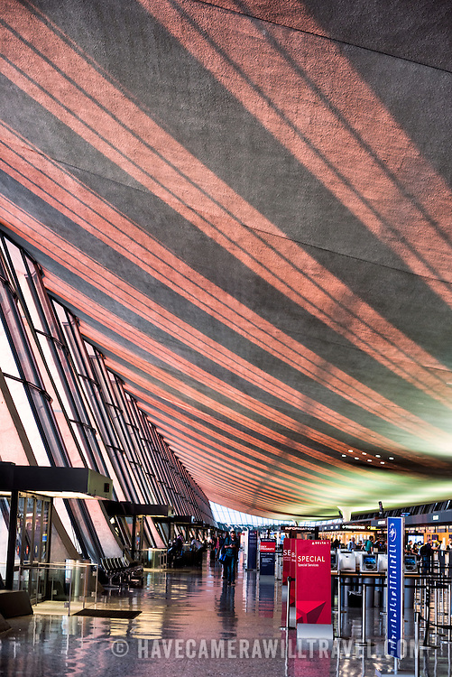 The late afternoon streams through large glass windows onto the ceiling of the original building, shaped like a wing, of Dulles International Airport in Chantilly, Virginia. Opened in 1962, Dulles Airport is one of three large airports serving the Washington DC region.