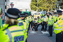 London, UK. 7 September, 2019. Metropolitan Police officers push activists off a zebra crossing as a vehicle approaches ExCel London on the sixth day of Stop The Arms Fair protests against DSEI, the world's largest arms fair. The sixth day of protests was billed as a Festival of Resistance and included performances, entertainment for children and workshops as well as activities intended to disrupt deliveries to ExCel London for the arms fair.