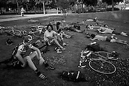 Picture by Andrew Tobin/Tobinators Ltd +44 7710 761829<br /> 04/08/2013<br /> Riders from Seattle in the USA and Edinburgh in Scotland relax on the grass in the evening during the Cycle Messenger World Championships held in Lausanne, Switzerland. Started in 1993 by Achim Beier from Berlin, the championships are not only a sporting contest but an opportunity to unite friends and bicycle enthusiasts worldwide. The event comprises a number of challenges including a sprint, a track stand (longest time stationary on the bike), a cargo race where heavy loads are carried on special bikes, and the main race. The course winds through central Lausanne and includes bridges, stairs, cobbles, narrow alleyways and challenging hills. The main race simulates the job of a bike courier making numerous drops and pickups across the city. Riders need to check in at specific checkpoints, hand over their delivery and get a new one. The main race can take up to 4 hours for each competitor to complete.