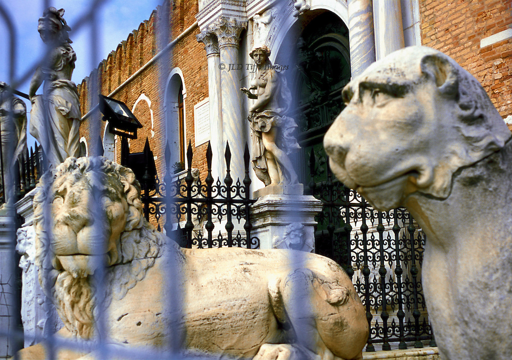 Venice, Arsenale gate and lion statuary through rails of fence.  The lion figures were taken from Greece, possibly Delos, in the 17th century..