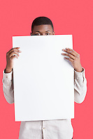Portrait of a young man holding blank cardboard in front of face over pink background
