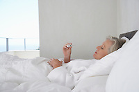 Mature woman lying in bed reading temperature from thermometer side view