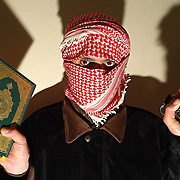 An anti occupation fighter holding a grenade and a copy of the Koran in Rutba, Iraq on the 23rd Dec 2003.