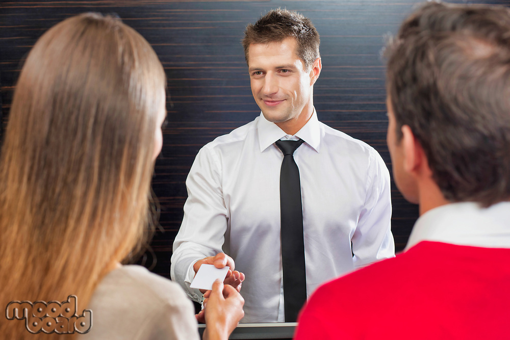 Hotel receptionist giving key card to the guest in lobby
