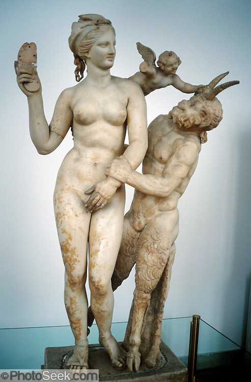 """National Archaeological Museum, Athens, Greece: a beautiful sculpture of Aphrodite, Eros, and Pan was found on Delos Island and dates from 100 BC. Aphrodite is the Greek goddess of  love, beauty, pleasure, sexuality, and procreation. She was born of Uranus, or else from parents Zeus and Dione. Her Roman equivalent was Venus. Aphrodite is also known as Cytherea (Lady of Cythera) and Cypris (Lady of Cyprus) after the two cult-sites which claimed her birth. Myrtles, doves, sparrows, horses, and swans are sacred to Aphrodite. Eros was the Greek god of love, whose Roman counterpart was Cupid (""""desire""""). Some myths make Eros a primordial god, while others say he is the son of Aphrodite. Pan, the companion of the nymphs, is the god of shepherds and flocks, nature, mountain wilds, hunting, rustic music, and theatrical criticism. Pan has the hindquarters, legs, and horns of a goat, like a faun or satyr. Pan's homeland of rustic Arcadia associates him with fields, groves, wooded glens, fertility, and the season of spring. In Roman religion and myth, Pan's counterpart was Faunus."""