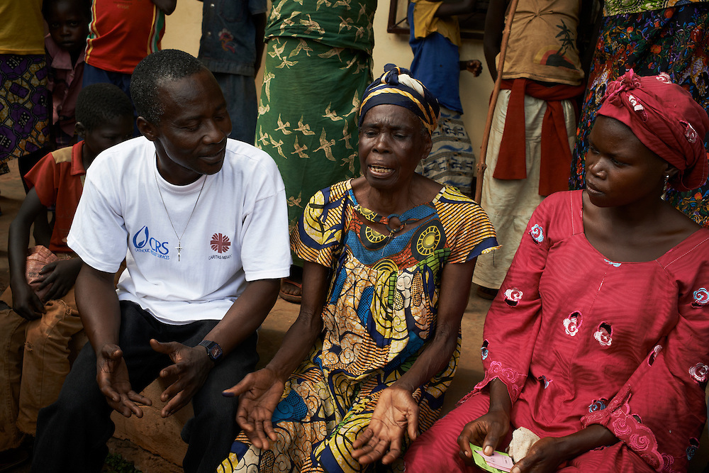 Beneficiary Yazam Lionnee  and her daughter Ngoungouwou talk with Julien Bakolo, Animateur, Caritas on a food voucher distribution day at the Hotel de Ville / Town Hall in the  town of Boda, Lobaye District, Central African Republic (CAR) on December 3, 2013. <br /> She is beneficiary of a CRS food voucher program. She does not work because of health problems and her husband is deceased, has 6 children and 9 grandchildren. She is 65 years old. <br /> <br /> Yazam Lionnee  - &ldquo;I have received vouchers worth 25,000 francs ($50) and will use them to buy manyok, rice, meat and smoked fish. This will support the family for a maximum of two weeks.  It&rsquo;s the first time I have participated in the project. My kids work in the fields, more so now since the mining has stopped in the region. Before they would do some mining and some agricultural work to bring home money. My health and the health of my family is the biggest problem that I face. I cannot work in the fields any longer so rely on my children to support the family. The current crisis in the country has impacted on the family&rsquo;s ability to get by. Before my family worked a bit in the mines and also the fields but we do not have the means now to support ourselves. We eat a meal of manyok two times per day with gambo (local vegetable). We cultivate our own manyok  in the fields. Occasionally we eat fruit and meat if we can afford it, maybe two times in the month. My husband was a Pasteur so I have a strong faith which helps me get through the crisis. I also have my family to thank for helping me get by. I ask that God protects us in this current crisis and all that passes in the future in CAR. &ldquo;<br /> <br /> CRS and partner organisation Caritas has provided immediate food security support to vulnerable households in the Lobaye Prefecture in the south west of CAR. Targeting 1,811 food insecure families, or 10,866 total beneficiaries, vouchers were distributed to vulnerable households which could be exchanged for food items at local markets. Th