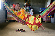 """Juchitan, Mexico:   Jose Antonio Sanchez Gomez, or """"La Mistica,"""" is a muxe, or transvestites, in the Oaxacan town of Juchitan. This is her one-room home, with an altar to her mother, and her hammock bed. She stands in a traditional, richly embroidered, Tejuana top and cool cotton skirt. Muxes are very common, and accepted, in this Southern Oaxacan region, which claims to not discriminate against gays. The matriarchal society is still driven by women but in flux in the machismo culture of Mexico. ,Sept. 14, 2008. (photo: Ann Summa)."""