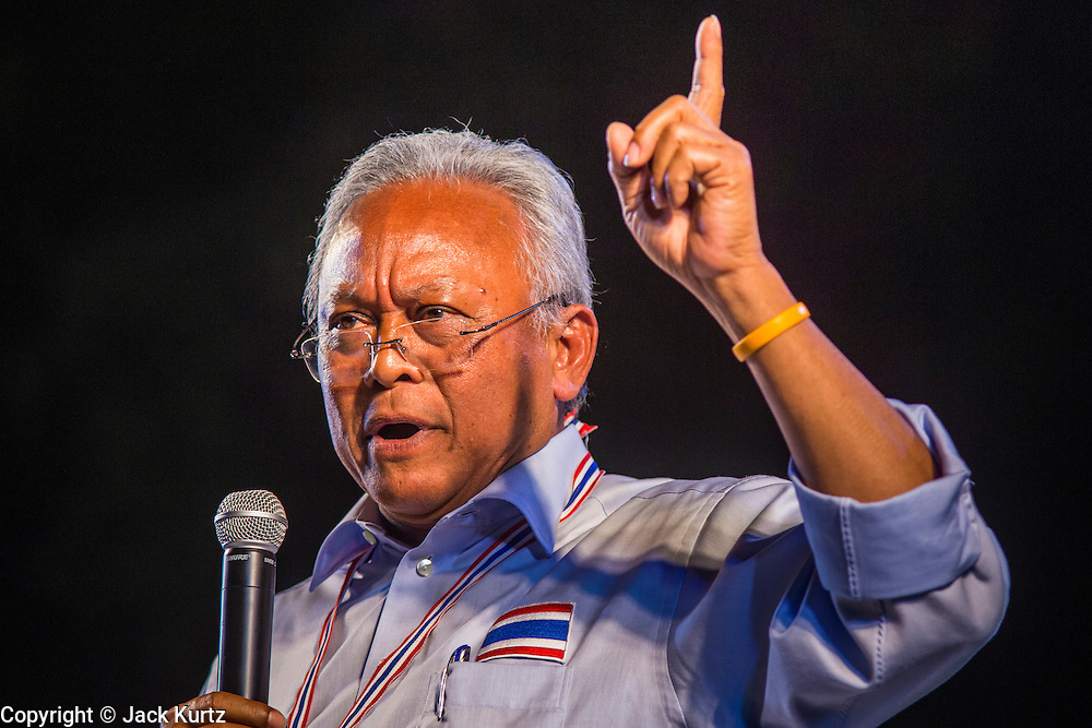 24 JANUARY 2014 - BANGKOK, THAILAND: SUTHEP THAUGSUBAN speaks on stage at the Shutdown Bangkok Pathum Wan site. Shutdown Bangkok has been going for 12 days with no resolution in sight. Suthep, the leader of the anti-government protests and the People's Democratic Reform Committee (PDRC), the umbrella organization of the protests,  is still demanding the caretaker government of Prime Minister Yingluck Shinawatra resign, the PM says she won't resign and intends to go ahead with the election.    PHOTO BY JACK KURTZ