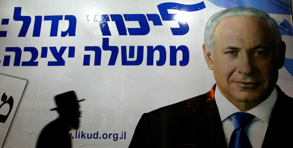 An ultra-Orthodox Jewish man passes an election campaign poster for the leader of the Likud Party, Benjamin Netanyahu   in Jerusalem on February. 5, 2009. Netanyahu leads Kadima party leader Tzipi Livni in polls leading up to national elections on Feb. 10, 2009.. Photo by Olivier Fitoussi /FLASH90