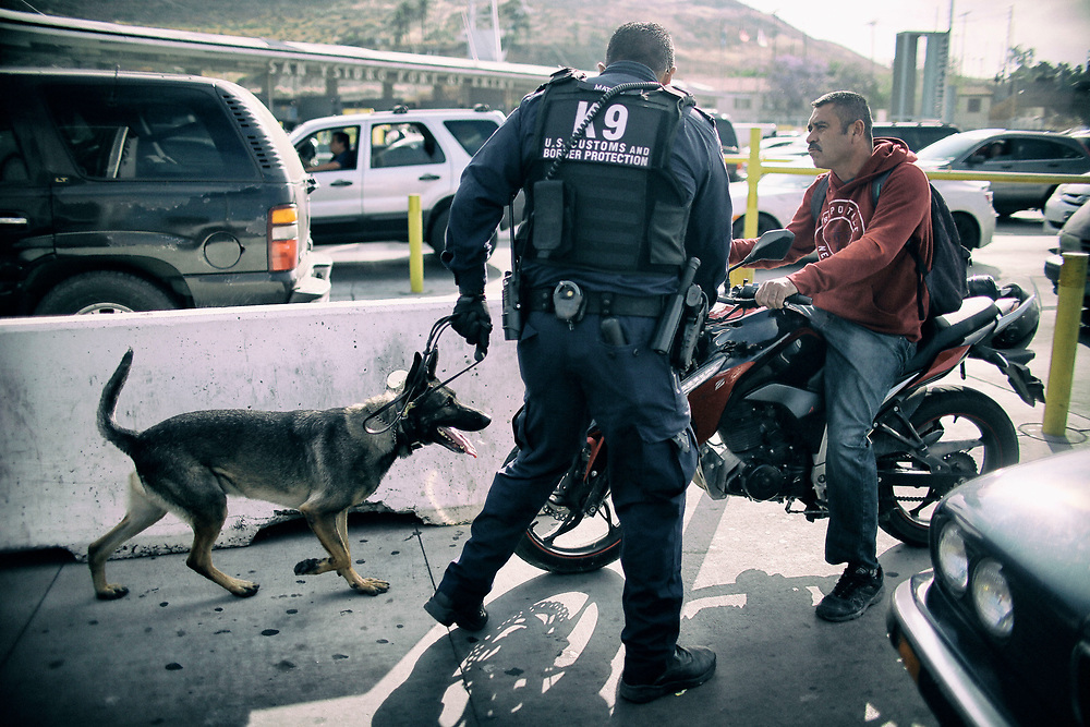 A Customs and Border Protection Agent and K-9 unit on patrol in theU.S. incoming auto line at the San Ysidro Port of Entry along the United States-Mexico border wall in San Ysidro, CA on Friday, June 9, 2017.(Photo by Sandy Huffaker for The New York Times)