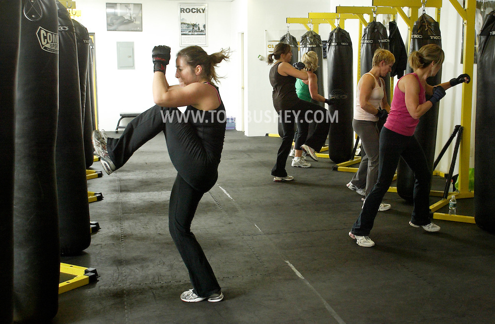 Melinda Stein, left, and other women work out during a fitness kickboxing class at Club KO Kickboxing in Warwick on Dec. 24, 2008.