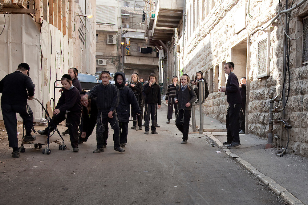 "A group of school kids get agitated by alien visitors and start throwing stones and yelling: ""Nazis!"". Mea Shearim remains an Old World enclave in the heart of Jerusalem. The overwhelmignly Haredi population has preserved the traditional ways of life that existed for centuries among the Orthodox Jews of Eastern Europe. Life revolves around disciplined adherence to Jewish law, prayer and the study of Jewish texts. The residents follow strict dress and speech customs deriving from 17th century ghettos. Mea Shearim was established in 1874 as the second settlement outside the walls of the Old City."