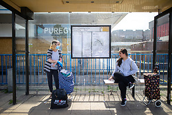 © Licensed to London News Pictures .  07/05/2020 . Salford, UK. Two women , one wearing a mask and gloves , remain at a distance from one another as they chat at a bus stop outside Shopping City in Salford . Photo credit : Joel Goodman/LNP