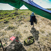 Cambodia has been dealing with the insurmountable task leftover from decades of war and its legacy, unexploded ordnance or UXOs. Estimates range from 3 to 9 million unexploded bombs that are still just beneath the surface throughout the region. These bombs are left over from air strikes, artillery fire, mortar shells, rockets, grenades, anti-personnel and anti-vehicle land mines are indiscriminate weapons and do not expire, often killing or injuring between 100 to 200 people in Cambodia a year. With little resource, the countries' people and Non Governmental Organizations (NGOs) are still facing over a hundred years being exposed to this deadly issue while walking and cultivating their land in fear.<br /> <br /> A rest area for Cambodian Mine Action Centre (CMAC) workers while they search for land mines and unexploded ordnance using a metal detector to sweep a field in the Cambodian countryside province of Kampong Thom. Jan. 2013.
