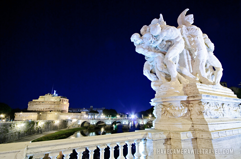 A night shot of the famous jail the Castel Sant'Angelo in Rome, Italy, with marble statues in the foreground decorating one of the bridges across the Tiber.