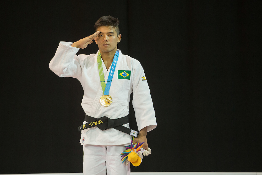 Gold medalist Charles Chibana salutes as the Brazilian national anthem is played during the medal ceremony for the men's judo 66kg class at the 2015 Pan American Games in Toronto, Canada, July 12,  2015.   AFP PHOTO/GEOFF ROBINS
