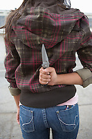 Young woman holding knife behind back
