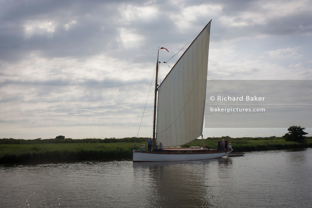 A large sailed yacht edges slowly down the River Bure near Ludham on the Norfolk Broads.