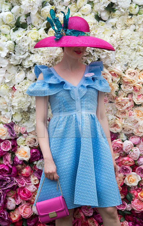 © Licensed to London News Pictures. 19/06/2018. London, UK.  A young woman in colourful clothing poses for a photograph while attending day one of Royal Ascot at Ascot racecourse in Berkshire, on June 19, 2018. The 5 day showcase event, which is one of the highlights of the racing calendar, has been held at the famous Berkshire course since 1711 and tradition is a hallmark of the meeting. Top hats and tails remain compulsory in parts of the course. Photo credit: Ben Cawthra/LNP