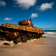 An abandoned tank, once used for target practice by the military, but now painted and a popular tourist attraction, sits half-submerged in the sand of Flamenco Beach, a world-famous beach located on the north shore of the island of Culebra, a satellite of Puerto Rico.