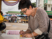 20 JULY 2015 - NONTHABURI, NONTHABURI, THAILAND: A woman inscribes a prayer on to a piece of wax that will be used to make candles for Buddhist temples on Nonthaburi Pier, the end of the Chao Phraya Express Boat line in Nonthaburi, a suburb of Bangkok. This is the north end of a plan to develop the Chao Phraya River riverfront. The Chao Phraya promenade is development project of parks, walkways and recreational areas on the Chao Phraya River between Pin Klao and Phra Nang Klao Bridges. The 14 kilometer long promenade will cost approximately 14 billion Baht (407 million US Dollars). The project involves the forced eviction of more than 200 communities of people who live along the river, a dozen riverfront  temples, several schools, and privately-owned piers on both sides of the Chao Phraya River. Construction is scheduled on the project is scheduled to start in early 2016. There has been very little public input on the planned redevelopment.          PHOTO BY JACK KURTZ