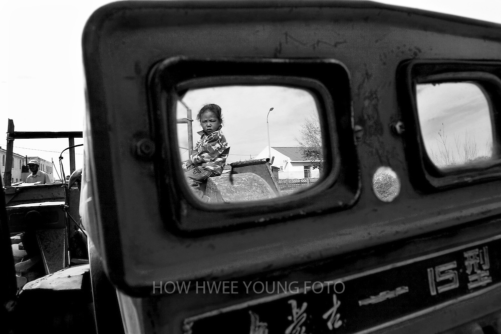 A young girl is seen through the windows of a tractor in Mongolia.