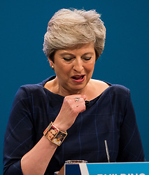 © Licensed to London News Pictures. 04/10/2017. Manchester, UK. British prime minister THERESA MAY attempts to clear her throat while delivering her leaders speech on the final day of the Conservative Party Conference. The four day event is expected to focus heavily on Brexit, with the British prime minister hoping to dampen rumours of a leadership challenge. Photo credit: Ben Cawthra/LNP