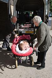 Staff wheeling physically disabled child towards ambulance,