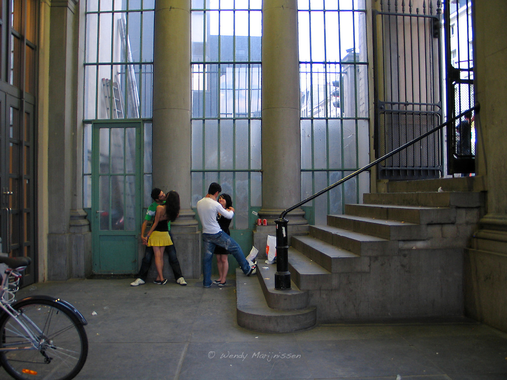 Two young couples are kissing and hugging in the entrance hall of Le Botanique. Brussels, Belgium
