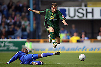 Darreb Huckerby for Norwich leaps over the tackle of Cardiffs Jermaine Darlington