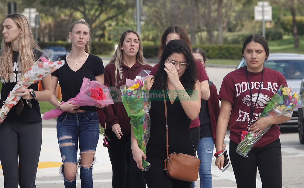 A group of mourners arrive with flowers at the memorial garden outside Marjory Stoneman Douglas High School in Parkland, Fla. on Wednesday, February 14, 2019, on the anniversary of the shooting at the school. Photo by Joe Cavaretta/Sun Sentinel/TNS/ABACAPRESS.COM