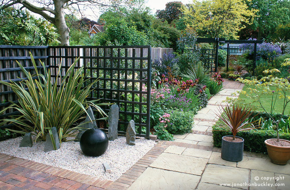 General view of Paul Kelly's garden showing oriental water feature, trellis dividers, stone paths and well planted border