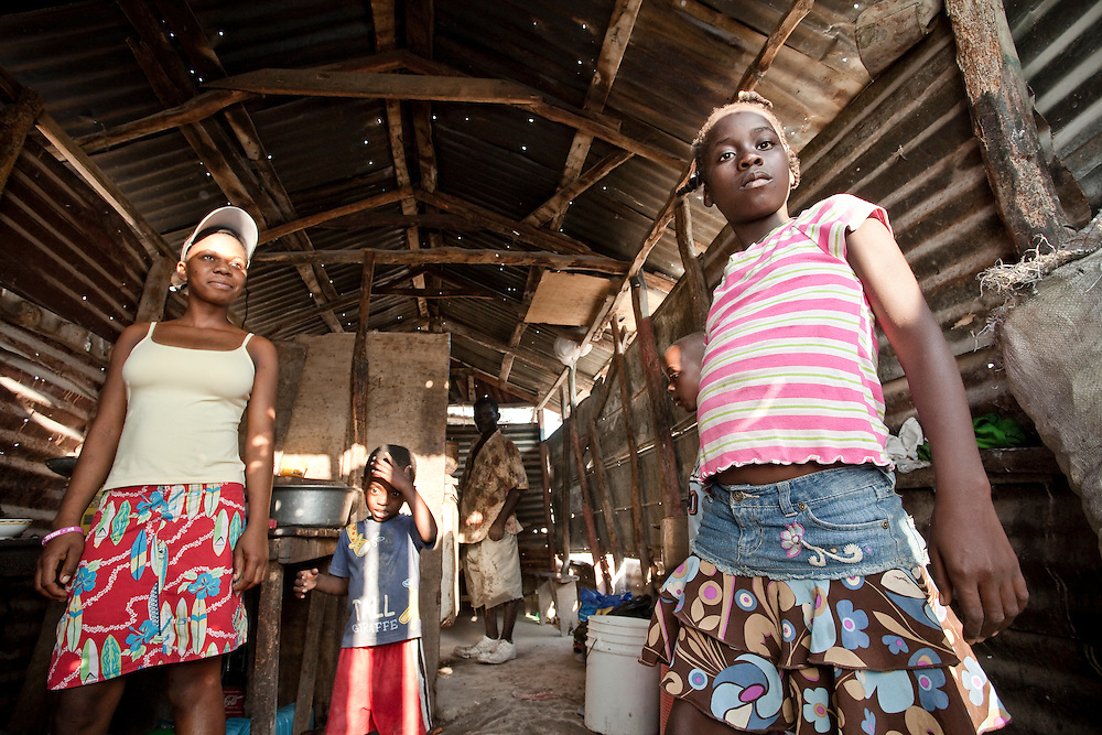 A family inside their home - a small hut made of corrugated iron - in Anse a Galet, Ile de la Gonave, Haiti