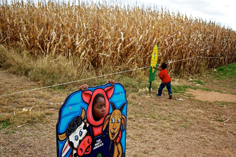 "Calvin Rodwell Elementary School Pre-kindergarten student Jordan Johnson, 5, left, poses in a cutout for a parent to take a photo at Summers Farm in Frederick, MD on Oct. 24, 2012. The visit to the farm was part of a ""Common Core"" reading and learning unit for their class, which aims to follow up non-fiction reading with learning in the field. The day prior the children read a book about going to a farm."
