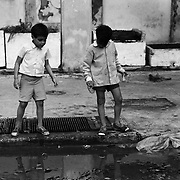 """The children of Havana.""  Two boys pass the time by breaking glass on the street."