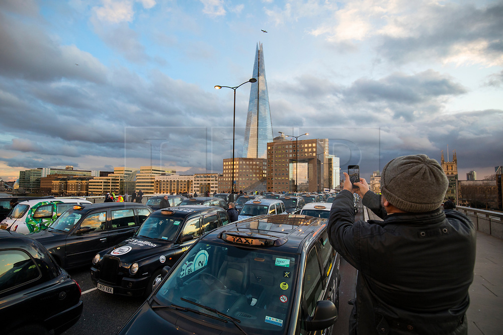 © Licensed to London News Pictures. 18/01/2018. London, UK. A passerby takes a photograph on his mobile phone as Black Cab drivers block London Bridge to protest against minicab firm Uber's continued operation in London. Transport for London revoked Uber's license in September 2017 but the decision is currently under appeal. Photo credit: Rob Pinney/LNP