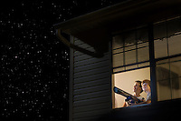 Teenage boys stand with telescope at open window looking at night sky