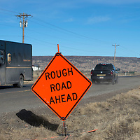 The North bound lane of Sakelares Boulevard in Grants has signs posted  warning drivers of the poor conditions of that stretch of road. The road is covered in uneven and covered in gravel and potholes.