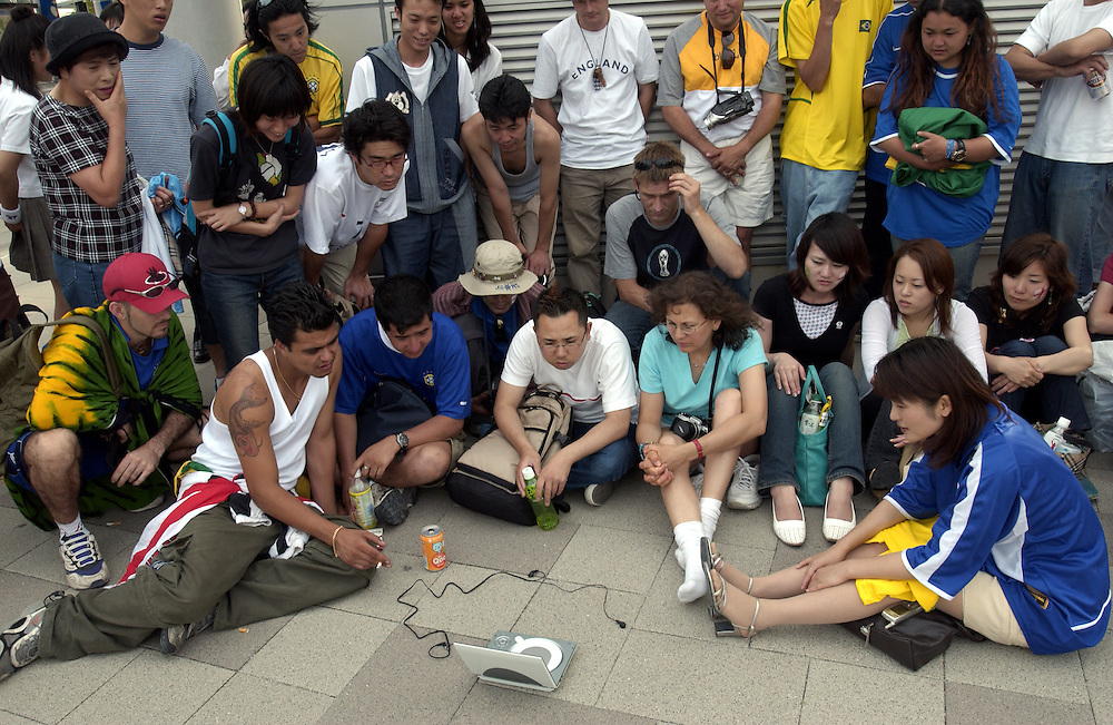 Soccer supporters, unable to buy illegal tickets from scalpers, settle for watching the match between England and Brazil on a small TV outside Shizuoka Station, in sight of Shzuoka Stadium. World Cup, Japan. 21/06/02..©David Dare Parker/AsiaWorks Photography