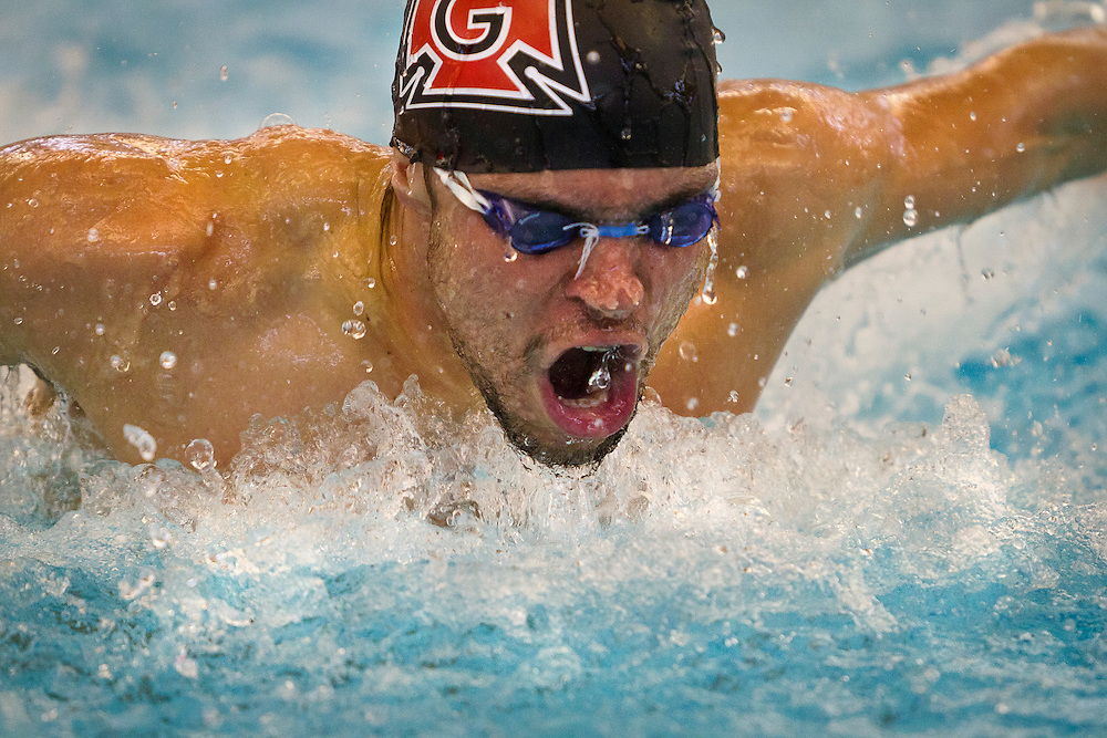 Chris Kaiser-Nyman '13 breaks out of the water during the Men's 100 yard Butterfly at the Grinnell College Pioneer Invitational.<br />