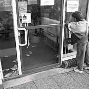 NLD/Bussum/19900926 - Overval Bondsspaarbank Koekkoeklaan Bussum, jongen kijkt door raam naar het verloren geld op de grond