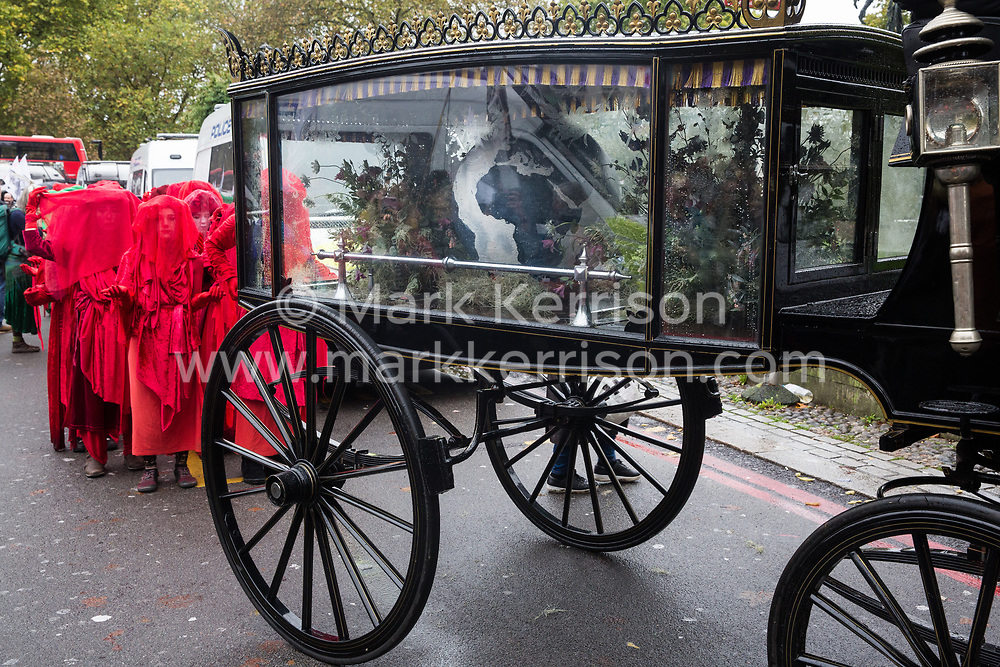 London, UK. 12 October, 2019. The Red Brigade assemble behind a horse-drawn hearse bearing a globe with thousands of fellow climate activists from Extinction Rebellion to take part in the XR funeral march from Marble Arch to Russell Square on the sixth day of International Rebellion protests to demand a government declaration of a climate and ecological emergency, a commitment to halting biodiversity loss and net zero carbon emissions by 2025 and for the government to create and be led by the decisions of a Citizens' Assembly on climate and ecological justice. Credit: Mark Kerrison/Alamy Live News