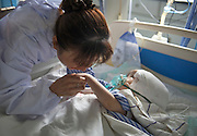 CHANGSHA, CHINA - JULY 15: (CHINA OUT) <br /> <br /> 3-year-old Girl Changes her oversize skull A 3D Printed Skull <br /> <br /> Hanhan's aunt holds her hand after Hanhan receiving an operation that changing her oversize skull with a 3D printed skull at the Second People\'s Hospital of Hunan Province on July 15, 2015 in Changsha, Hunan Province of China. 3-year-old girl Hanhan's congenital hydrocephaly with 85 percent hydrocephaly made her skull 3 times bigger than the formal ones. Doctors of the Second People\'s Hospital of Hunan Province used 3D printing technology create a titanium alloy skull and made a 17-hour operation to set it on Hanhan's head successfully. <br /> ©Exclusivepix Media
