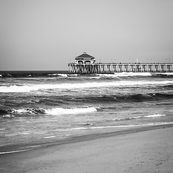 Huntington Beach Pier black and white photo. Huntington Pier is a registered historic place and has a Ruby's Restaurant at the end. Huntington Beach is a seaside beach city along the Pacific Ocean in Orange County Southern California and is also known as Surf City USA. Copyright © 2012 Paul Velgos with All Rights Reserved.