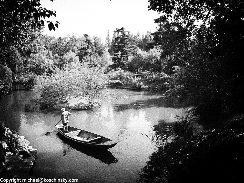 Black and white photo of chinese gardener on a boat drifting on a pond