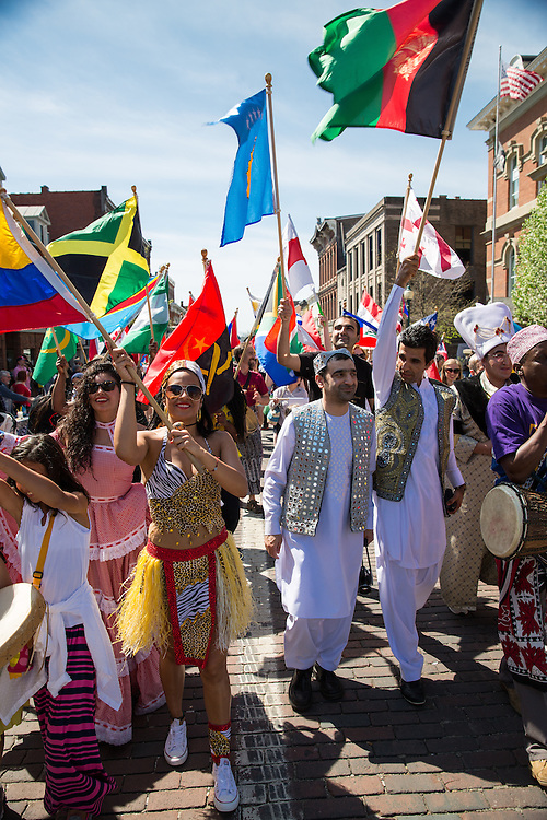 Participants march and waive flags during the annual International Street Fair parade.