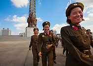 Smiling North Korean female soldiers at the Tower of the Juche Idea in Pyongyang, North Korea.