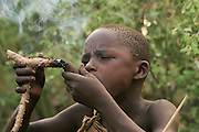 Africa, Tanzania, Lake Eyasi, young male Hadza child smoking from a traditional clay pipe. A small tribe of hunter gatherers AKA Hadzabe Tribe