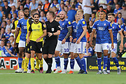 Referee Ross Joyce calms players down during the EFL Sky Bet League 1 match between Burton Albion and Ipswich Town at the Pirelli Stadium, Burton upon Trent, England on 3 August 2019.