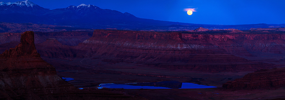 The full moon rises over canyon rims overlooking potash drying pools on the Colorado River near Moab, Utah. The La Sal Mountains are visible in the distant background.<br />